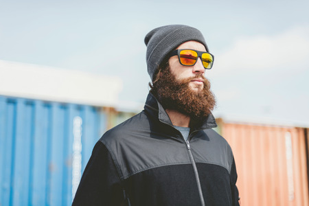 young unshaven: Close up Pensive Young Man with Unshaven Beard, Wearing Black Jacket, Bonnet and Sunglasses, Looking to the Right Seriously.