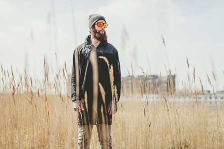 observant: Casual bearded man wearing trendy sunglasses and a coat standing waiting in an empty field amongst the long dried grass