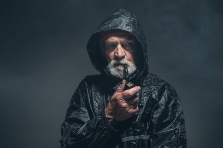 oldage: Portrait of a Reflective Bearded Old Guy in Black Rain Jacket, Smoking a Cigarette Using a Pipe. Captured in Studio. Stock Photo