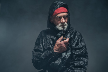 oldage: Close up Bearded Elderly Man in Black Winter Outfit with Smoking Pipe, Looking To the Right of the Frame Seriously Against Fuzzy Background at the Studio.