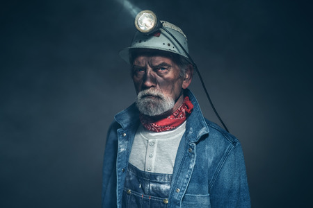 Close up Humorless Bearded Elderly Miner in Denim Jacket and Helmet, Staring at the Camera on a Blurry Background.
