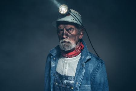 Close up sin humor Miner Ancianos barbudo en Chaqueta Tejana y casco, mirando a la cámara sobre un fondo borroso.