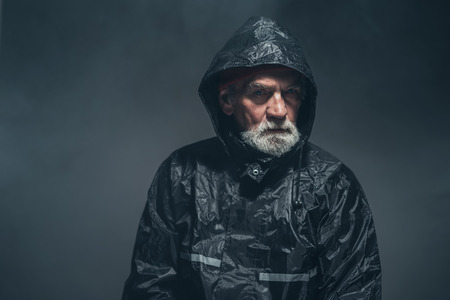 sombre: Close up Humorless Bearded Old Man in Black Rain Jacket Looking Straight at Camera Against Black Background.