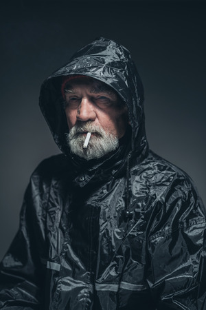 contemplative: Close up Contemplative Old Bearded Man in Black Raincoat with Smoke, Looking Into Distance Seriously Against Black Background.