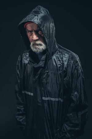 personne en colere: Half Body Shot d'un homme senior barbu vêtu de noir Sérieux Raincoat, à regarder la caméra. Isolé sur fond noir.