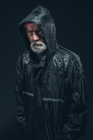 glowering: Half Body Shot of a Serious Bearded Senior Man Wearing Black Raincoat, Staring at the Camera. Isolated on Black Background. Stock Photo
