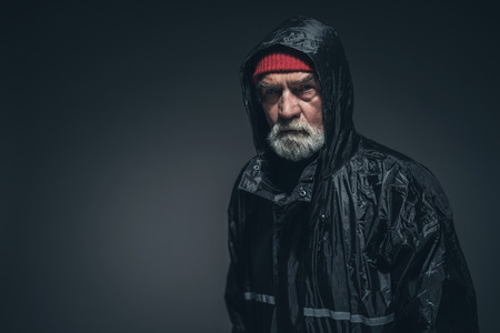 oldage: Bearded Adult Man Wearing Black Waterproof Jacket, Looking at the Camera Seriously Against Black Background with Copy Space.