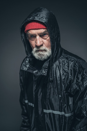 slicker: Close up Elderly Man with White Facial Hair, Wearing Red Bonnet and Black Rain Slicker, Looking Straight at the Camera. Captured in Studio with Black Background.