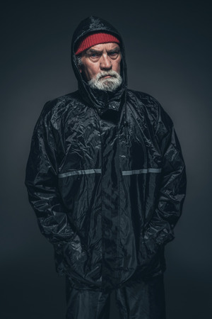 oldage: Portrait of a Serious Adult Guy with White Facial Hair, Wearing Black Winter Clothing, Looking Straight at the Camera Against Black Background.