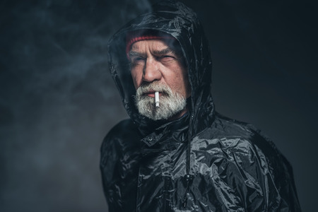 sombre: Close up Bearded Adult Guy in Waterproof Jacket, Smoking a Cigarette in a Pensive Facial Expression. Captured in Studio with Black Background.