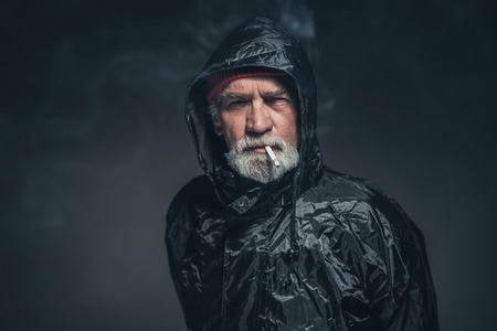 sombre: Portrait of a Serious Old Guy with Facial Hair in Rain Slicker Outfit, Smoking a Cigarette While Looking Straight at the Camera on a Black Background.