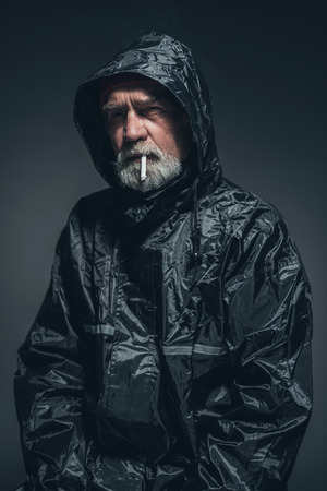 senior smoking: Portrait of a Reflective Senior Man in Black Rain Jacket, Smoking a Cigarette While Looking Into Distance.
