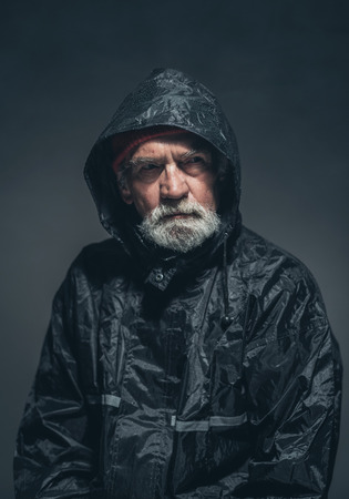 oldage: Close up Serious Adult Guy with Beard and Mustache, Wearing Black Rain Jacket, Looking at the Distance While Thinking of Something. Captured in Studio with Black Background.