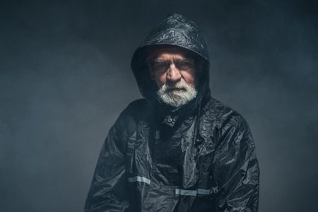 unemotional: Portrait of a Bearded Senior Man in Black Waterproof Jacket, Looking at the Camera on a Fuzzy Black Background in the Studio.