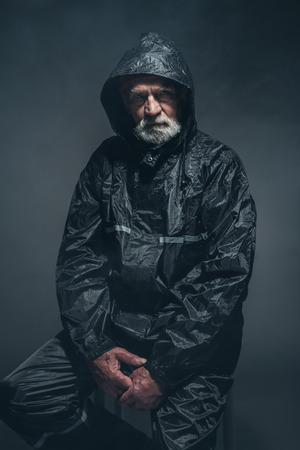 oldage: Portrait of a Serious Bearded Senior Man in Black Raincoat, Sitting on a Stool and Looking at the Camera Against Black Background.