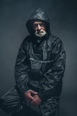 hombre barba: Retrato de un hombre mayor barbudo serio en Negro Gabardina, sentado en un taburete y mirando a la cámara contra el fondo Negro. Foto de archivo
