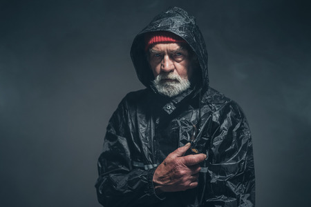 oldage: Bearded Serious Man Wearing Black Winter Outfit, Looking Straight at the Camera Against Fuzzy Black Background.