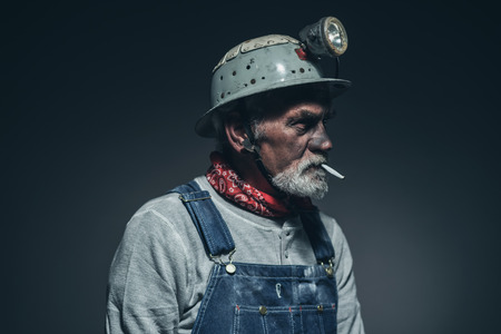 the miner: Close up Bearded Elderly Male Gold Miner Smoking a Cigarette While Facing to the Right of the Frame Against Black Gradient Background