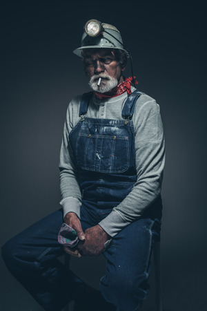 overseer: Portrait of an Active Senior Bearded Miner Guy with Smoke on her Mouth, Sitting on a Stool and Holding his Gloves While Looking Straight at the Camera Against Gray Gradient Background.