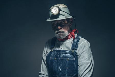 mineria: Cierre de la Edad Media Hombre mina Trabajador con Girado Luz en su casco, mirando a la c�mara en serio contra el fondo gris degradado.