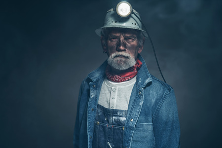 Close up Adult Male Gold Miner with Dirt and Facial Hair on his Face, Staring at the Camera on a Fuzzy Black Background.