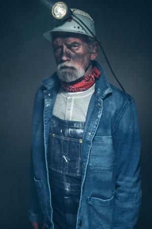 prospector: Close up barbudo masculino mayor mina Trabajador, vistiendo chaqueta de dril de algodón y casco con lámpara, mirando directamente a la cámara en una expresión facial seria.