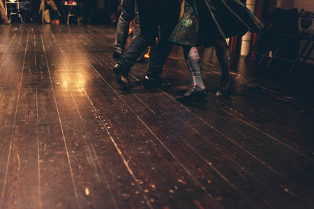 Feet of a man and woman dancing on an old wooden floor with a glowing reflection of candles or a light on the surface of the wood