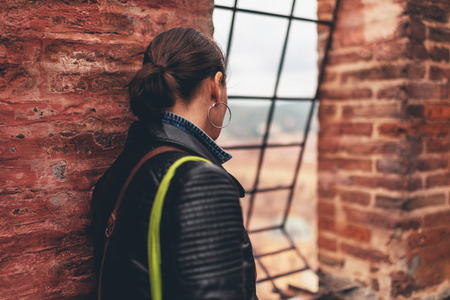 guarded: Thoughtful woman tourist leaning on a brick wall of an old building as she looks through an opening in the wall guarded by a metal grid at the town below Stock Photo