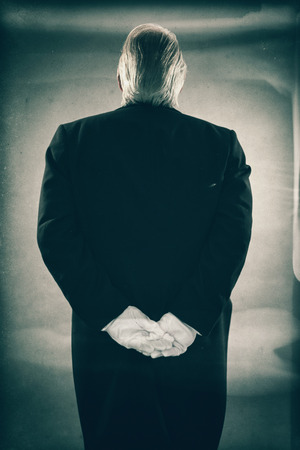 Rear View of Senior Male Butler Wearing Suit Standing at Attention with White Gloved Hands Clasped Behind His Back