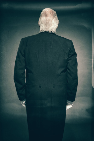 deportment: Rear View of Senior Male Butler with Grey Hair Wearing Suit and White Gloves Standing at Attention