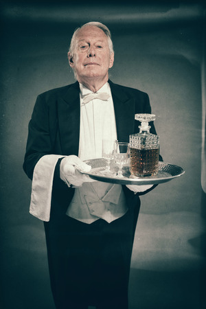 cordial: Professional Looking Senior Male Butler Wearing Tuxedo and Carrying Tray with Liquor Bottle and Two Crystal Cordial Glasses
