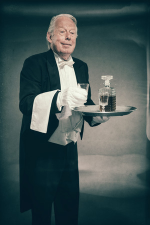 Senior Male Butler Wearing Tuxedo and Serving from Tray with Liquor Bottle and Crystal Cordial Glasses