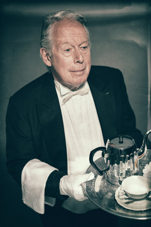 High Angle View of Professional Looking Senior Male Butler Wearing Tuxedo and Carrying Tray with Tea Service for One with Tea Pot and Cup and Saucer