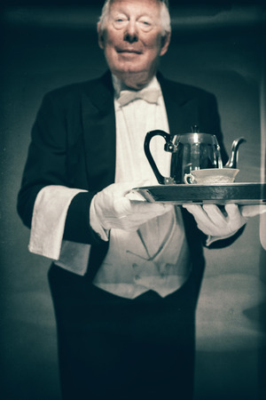 servitude: Portrait of Friendly Looking Senior Male Butler Wearing Tuxedo and Holding Tray with Tea Service for One with Pot and Cup Stock Photo