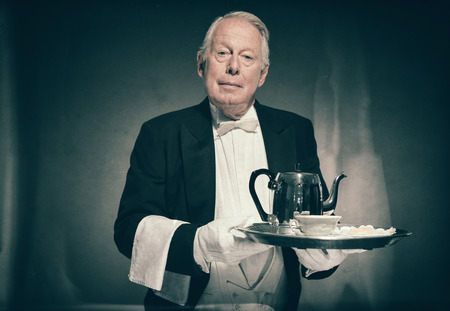 deportment: Waist Up Portrait of Professional Looking Senior Male Butler Wearing Tuxedo and Holding Tray with Tea Service for One with Pot and Cup