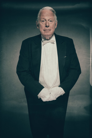Senior Male Butler Wearing Formal Tuxedo Suit and White Gloves Standing at Attention Ready for Service and Looking at Camera