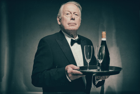 deportment: Waist Up Portrait of Professional Looking Senior Male Butler Wearing Suit with Bow Tie and Carrying Tray with Bottle of Champagne and Two Glass Flutes