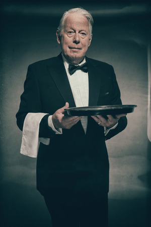 product placement: Portrait of Friendly Looking Senior Male Butler Wearing Formal Tuxedo Suit Carrying White Towel Over Arm and Empty Tray Stock Photo