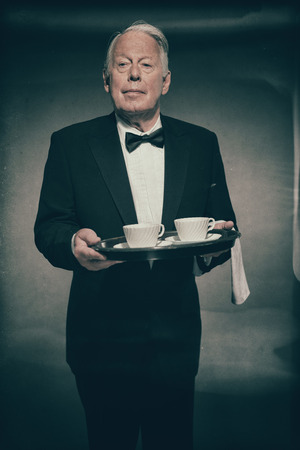 deportment: Portrait of Refined Looking Senior Male Butler Wearing Formal Tuxedo Suit and Carrying Tray of White Coffee Mugs or Tea Cups