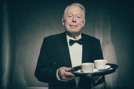 deportment: Senior Male Butler Wearing Formal Suit and Bow Tie Holding Tray with Two White Coffee Cups in Dimly Lit Studio