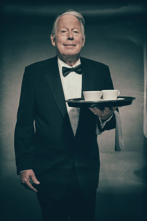 deportment: Smiling Senior Male Butler Wearing Formal Suit and Bow Tie Holding Tray with Two White Coffee Cups in Dimly Lit Studio
