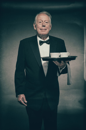 dimly: Smiling Senior Male Butler Wearing Formal Suit and Bow Tie Holding Tray with Two White Coffee Cups in Dimly Lit Studio