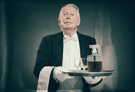 Professional Looking Senior Male Butler Wearing Tuxedo and Carrying Tray with Liquor Bottle and Two Crystal Cordial Glasses