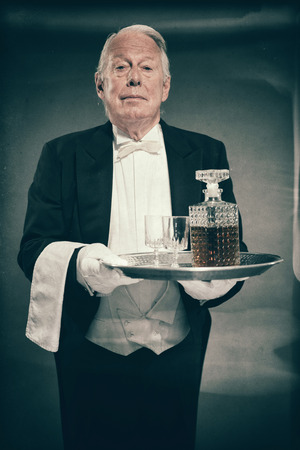 deportment: Professional Looking Senior Male Butler Wearing Tuxedo and Carrying Tray with Liquor Bottle and Two Crystal Cordial Glasses