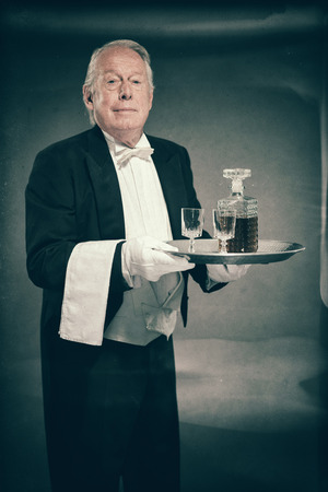 deportment: Professional Looking Senior Male Butler Wearing Tuxedo and Carrying Tray with liquor Bottle and Two Crystal Cordial Glasses Stock Photo