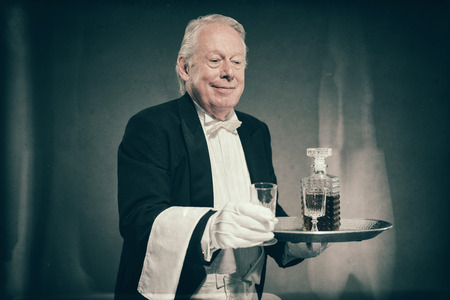 cordial: Senior Male Butler Wearing Tuxedo and Serving from Tray with Liquor Bottle and Crystal Cordial Glasses