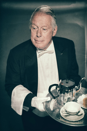 deportment: High Angle View of Professional Looking Senior Male Butler Wearing Tuxedo and Carrying Tray with Tea Service for One with Tea Pot and Cup and Saucer