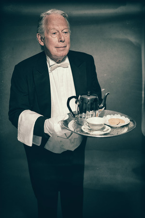 deportment: High Angle View of Professional Looking Senior Male Butler Wearing Tuxedo and Carrying Tray with Tea Service for One with Tea Pot, Cup and Saucer, and Cookie Biscuits