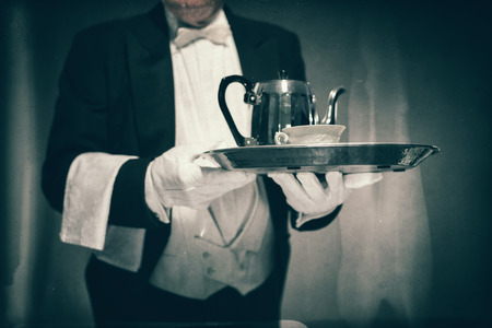 deportment: Close Up of Male Butler Wearing Tuxedo and Holding Tray with Tea Service for One with Pot and Cup Stock Photo