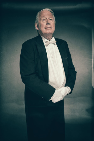 deportment: Senior Male Butler Wearing Formal Tuxedo Suit and White Gloves Standing at Attention Ready for Service and Looking at Camera